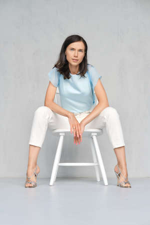 Beautiful and happy young lady in blue satin blouse, white jeans and silver stilettos sitts on white chair in studio