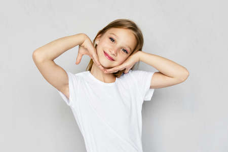 Young angry and mischievous girl in white t-shirt and jeans shorts posing in studio