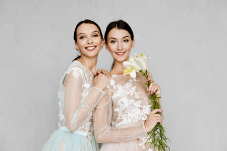 Two beautiful girls in transparent tulle dresses with lace posing in identical manner