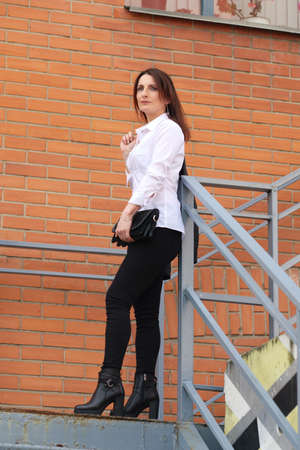 Young woman in black tight jeans and white shirt goes down the stairs 写真素材
