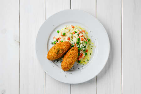 Top view of cutlet stuffed with cheese served with rice, green pea and carrot on white wooden table 写真素材