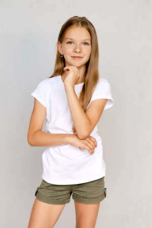 Full length portrait of positive teenager girl standing straight with both hands in pockets