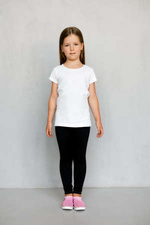 Cute young child with long hair in t-shirt and sweatpants standing with arms spread apart 写真素材