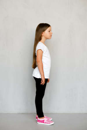 Cute young child with long hair in white t-shirt and black sweatpants posing 写真素材