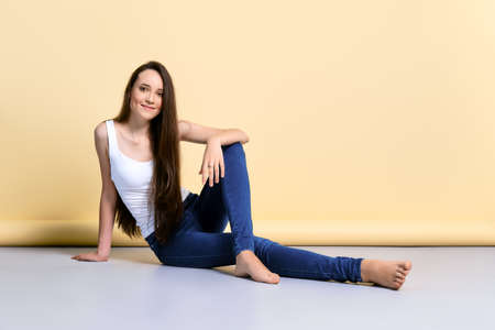 Barefoot young woman in white tank top and jeans sitting on the flook in studio 写真素材