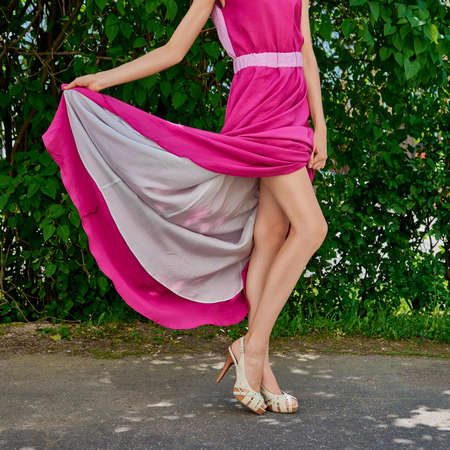Cropped image of female legs in stilettos lifting the hem of long dress outdoor