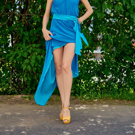 Cropped image of bare female legs in stilettos lifting the hem of long dress outdoor