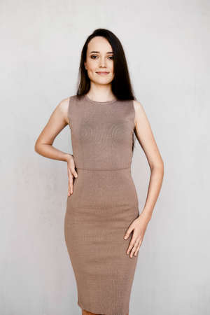 Lovely young woman in tight knitted dress, long straight black hair and high heel shoes posing in studio