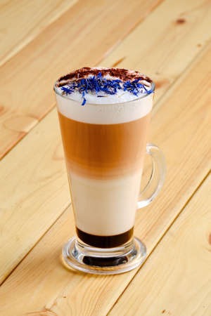 Latte macchiato with chocolate and dry knapweed petals in transparent glass on wooden background