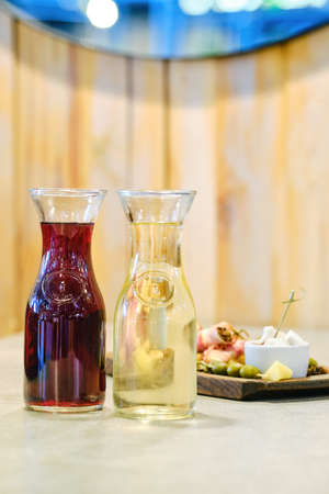 Two decanters with wine and plate with snack on background (soft focus photo with shallow depth of field)