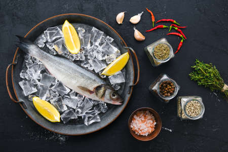 Raw seabass fish with spice and herbs on wooden background