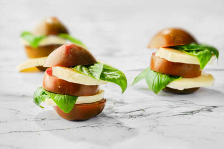 Brown chocolate tomato, mozzarella and basil cutted on slices and stacked on marble background (selective focus photo)