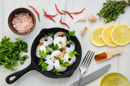 Top view of pan with fresh raw prawn with spice and herbs