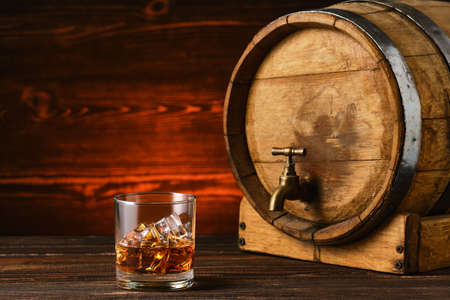 Glass of whiskey with ice with barrel on background