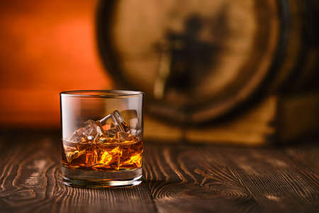 Glass of whiskey with ice with barrel on background (soft focus photo with shallow deph of field)