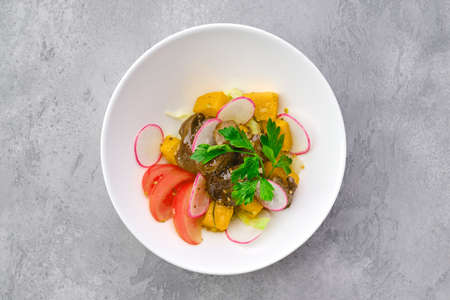 Top view of salad with fried chicken liver, radish, pumpkin, tomato and mustard