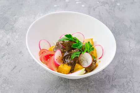Portion of salad with fried chicken liver, radish, pumpkin, tomato and mustard