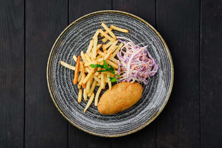 Top view of Kiev cutlet with american fries and red cabbage with carrot as a garnish Standard-Bild