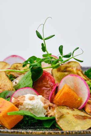 Macro photo of salad with soft cheese, radish, pear, pumpkin and sun dried tomato