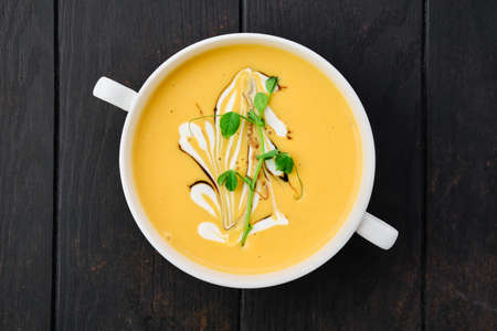 Top view of pumpkin puree soup with barbecue sauce and sour cream