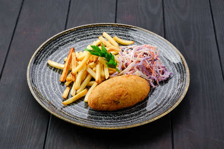 Kiev cutlet with american fries and red cabbage with carrot as a garnish