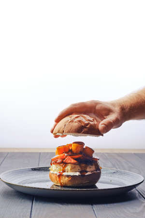 Making burger with beef, bacon, pumpkin and tomato - male hand puts bun on the top