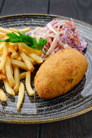 Close up view of Kiev cutlet with american fries and red cabbage with carrot as a garnish