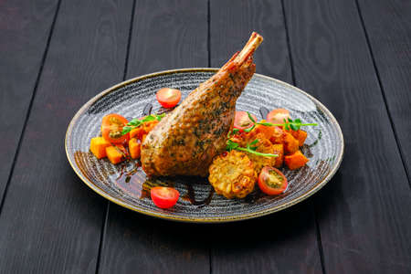 Roaster turkey leg with fried pumpkin and grilled corn decorated with tomato