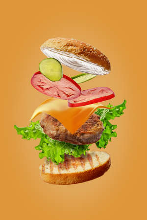 Burger with flying ingredients isolated on orange background Foto de archivo
