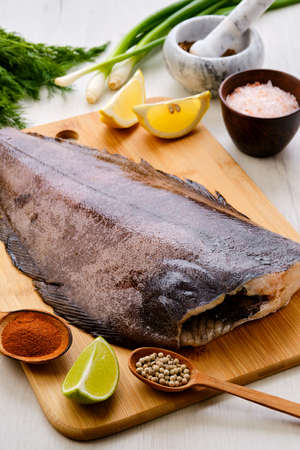 Raw fresh halibut without head on wooden cutting board