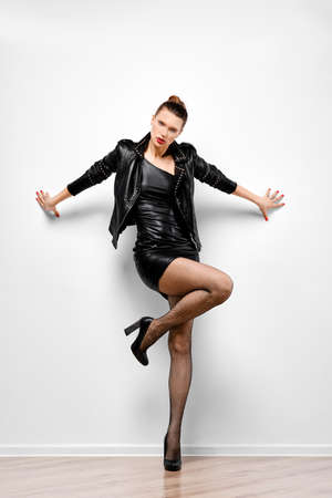 Studio portrait of trendy woman in leather jacket and shorts with natural make up and red lips