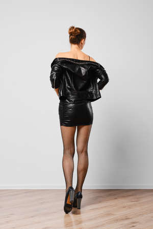 Studio portrait of trendy woman in leather jacket and shorts with natural make up and red lips Foto de archivo