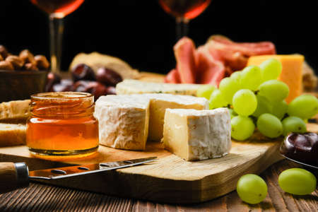 Close up view of brie cheese on plate with snack for wine (focus on foreground) Reklamní fotografie