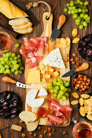 Top view of cheese plate with dorblu, brie, cheddar, prosciutto, grapes, honey, dates, crackers, nuts and wine on a wooden background