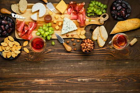 Top view of cheese plate with prosciutto, grapes, honey, dates, crackers, nuts and wine on a wooden background with copy space
