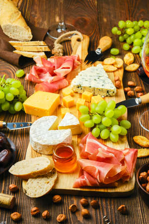 Cheese plate with dorblu, brie, cheddar, prosciutto, grapes, honey, dates, crackers, nuts and wine on a wooden background