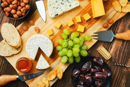 Top view of cheese plate with dorblu, brie, cheddar, grapes, honey, dates, crackers and nuts on a wooden background