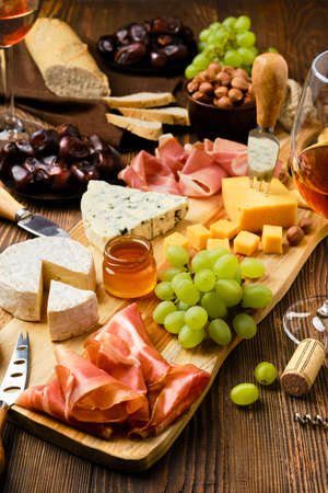Cheese plate with prosciutto, grapes, honey, dates, crackers, nuts and wine on a wooden background with copy space