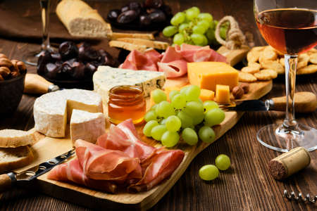 Cheese plate with prosciutto, grapes, honey, dates, crackers, and wine on a wooden background (focus on foreground)