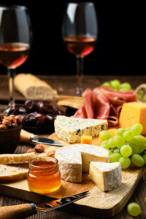 Cheese plate with prosciutto, grapes, honey, dates, crackers, and wine on a wooden background