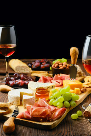 Plate with prosciutto, grapes, honey, dates, crackers, nuts and wine on a wooden background with copy space