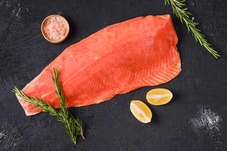 Raw frozen salmon fillet on dark background