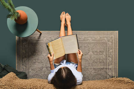 Cute African American woman sitting on the floor near the bed and reading a book (view from above) 版權商用圖片
