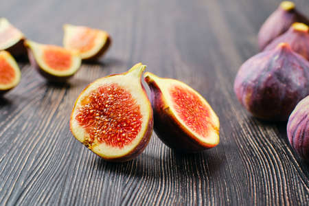 Fresh figs, whole and cut on slices on wooden table