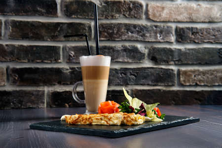 Omelette with salmon on slate plate and cup of latte Stok Fotoğraf