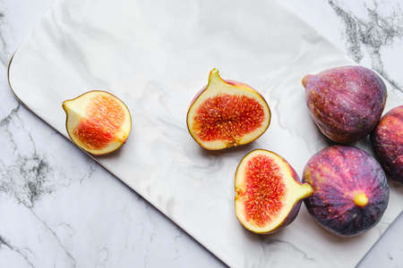 Top view of fresh figs, whole and cut on slices on marble plate Banco de Imagens