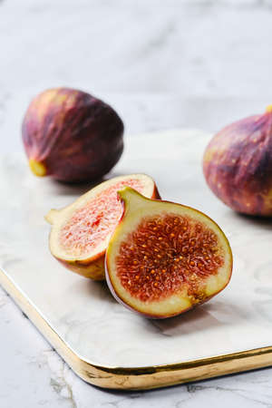 Fresh figs, whole and cut on slices on marble plate