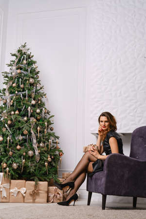 Fashionable woman posing in armchair near christmas tree and fireplace, showing legs in old-fashioned stockings