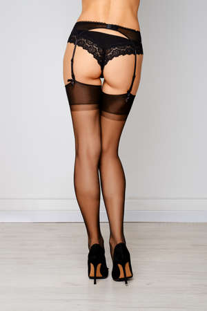 Back view of beautiful female legs in stockings, garter belt and panties Banque d'images