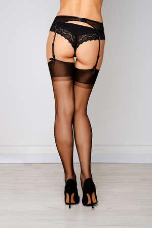 Back view of beautiful female legs in stockings, garter belt and panties Stock Photo
